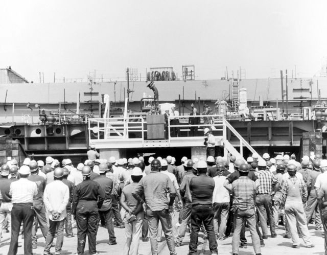 Workmen at Ingalls Shipbuilding, Inc. listen as General Alfred M. Gray Jr., commandant of the Marine Corps, speaks during keel laying ceremony for the LHD-class amphibious assault ship USS ESSEX (LHD 2). J St. Pe', president, Ingalls Shipbuilding, Inc., and E.E. Shoults, program manager, Amphibious Warfare and Strategic Sea Lift Program, are pictured in the background