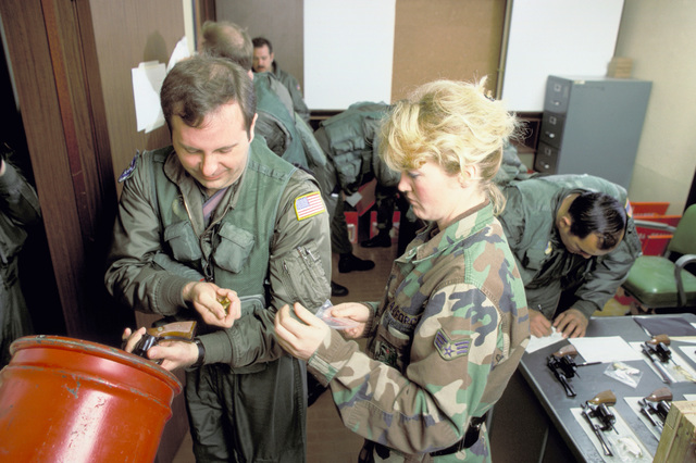 A member of the 435th Tactical Airlift Wing issues survival vests and handguns to flight personnel. They are preparing for an air drop conducted as part of an Army training and evaluation program (ARTEP) mission