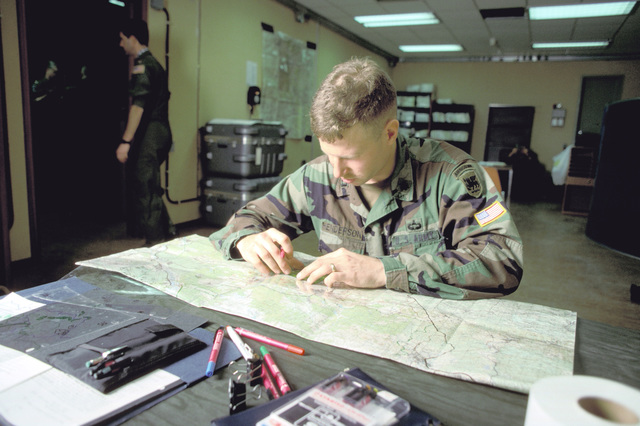 Army CPT Robert Henderson, Airborne Combat Team, 3rd Battalion, 325th Infantry Divion plots coordinates for an airborne jump which is part of an Army training and evaluation program (ARTEP) mission