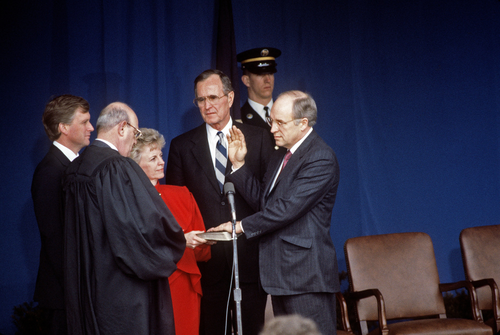 Laurence H. Silberman, circuit court judge, Washington, District of Columbia (DC) Court of Appeals, swears in Richard B. Cheney, secretary of defense.  Mrs. Cheney holds the Bible during the ceremony at the Pentagon as President George H.W. Bush, and Vice President J. Danforth Quayle look on