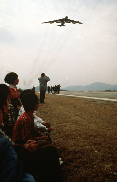 A 320th Bombardment Wing (320th BMW) B-52 Stratofortress aircraft passes over a group of civilians gathered along a highway landing strip during the joint South Korean/United States exercise TEAM SPIRIT '89