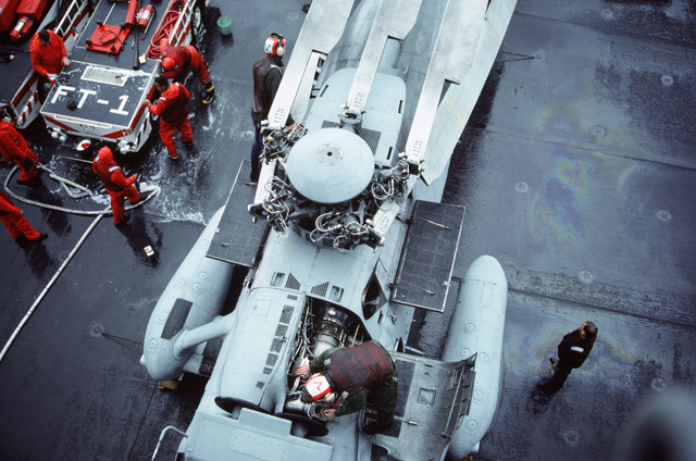An overhead view of crewmen performing maintenance on an SH-3H Sea King helicopter from Helicopter Anti-submarine Squadron 5 (HS-5) on board the nuclear-powered aircraft carrier USS DWIGHT D. EISENHOWER (CVN 69).  At left, damage control/firefighting personnel wash down a vehicle.  The EISENHOWER is conducting carrier qualifications off the Virginia Capes