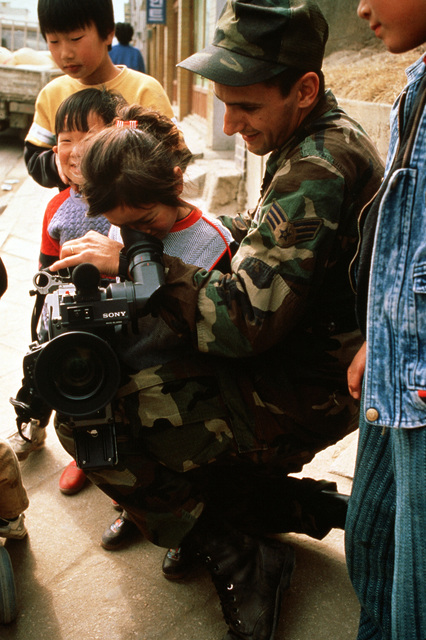 Sergeant Steve Ninotta, a video camera technician with the 1365th Audiovisual Squadron (1365th AVS), allows a child to look through the viewfinder of his camera during the joint South Korean/United States exercise TEAM SPIRIT '89