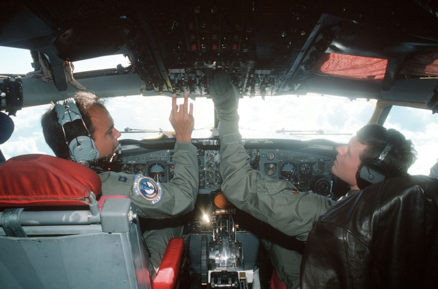 Pilot CPT Kurt Lajala, left, and co-pilot 1LT Steve Hazelfeldt check some of the instruments in the cockpit of a KC-135 Stratotanker aircraft during a flight out of Andersen Air Force Base, Guam, during exercise Giant Warrior '89. The two officers are members of the 906th Air Refueling Squadron