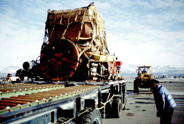 A civilian employee checks the position of a pallet equipment on a K-loader. The equipment, which was brought to Alaska aboard a 3rd Military Airlift Squadron C-5B Galaxy aircraft, will be used in the cleanup of the oil spilled by the tanker Exxon Valdez in Price William Sound