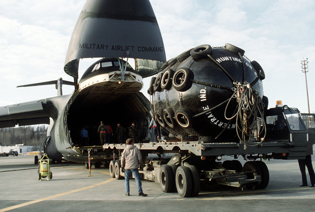 Members of the 616th Aerial Port Squadron unload equipment from a 3rd Military Airlift Squadron C-5B Galaxy aircraft onto a K-loader. The equipment will be used in the cleanup of the oil spilled by the tanker Exxon Valdez in Price William Sound