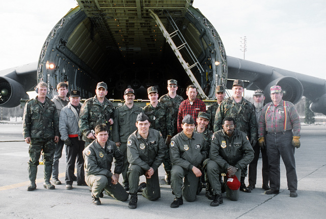 The men who unloaded a 3rd Military Airlift Squadron (3rd MAS) C-5B Galaxy aircraft gather in front of the aircraft after their work is done. Four members of the 3rd MAS kneel in the front row; five civilians and eight members of the 616th Aerial Port Squadron are behind them. The aircraft carried equipment that will be used in the cleanup of the oil spilled by the tanker Exxon Valdez in Price William Sound