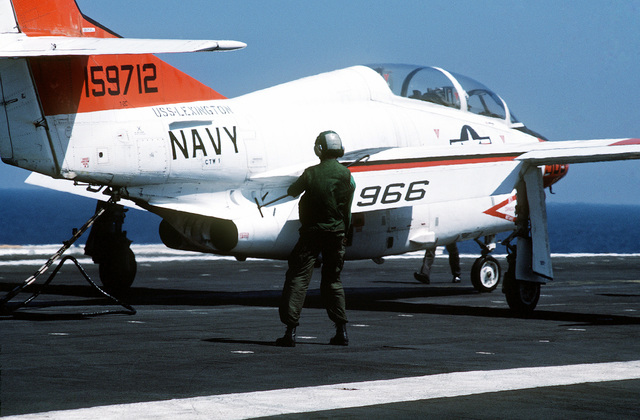 A hook runner stands ready to disengage the crossdeck pendant from the tailhook of a T-2C Buckeye aircraft on the flight deck of the auxiliary aircraft landing training ship USS LEXINGTON (AVT 16) during pilot carrier training in the Gulf of Mexico