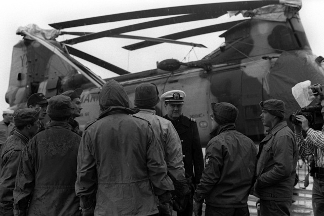 A lieutenant commander talks with a group of sailors on the flight deck of the dock landing ship USS JUNEAU (LPD-10). Behind them is a CH-46E Sea Knight helicopter from Marine Medium Helicopter Squadron 166 (HMM-166). The JUNEAU is in Alaska to provide support for the military and civilian personnel involved in the cleanup of the oil spilled when the tanker EXXON VALDEZ ran aground in Prince William Sound on March 24