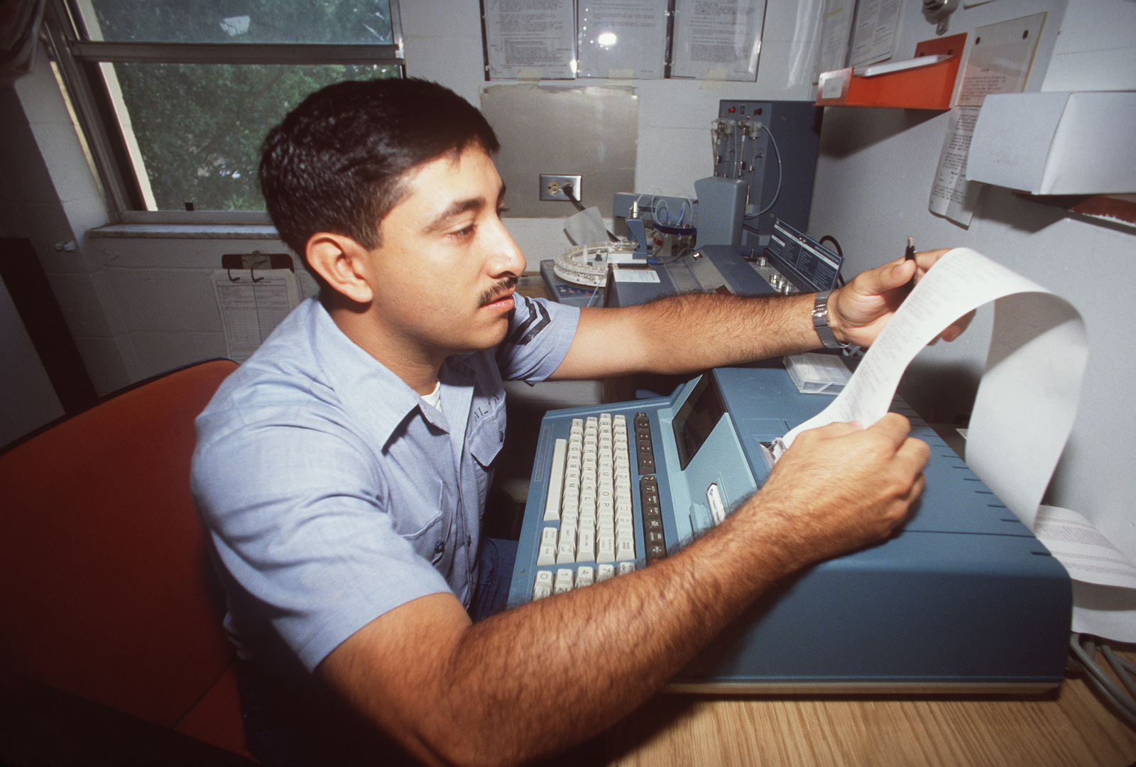 A technician examines a printout of results from the testing of urine samples for the presence of THC, cocaine, PCP, opiates, and amphetamines, in the Department of Defense's program to screen job applicants and some employees for use of illegal drugs