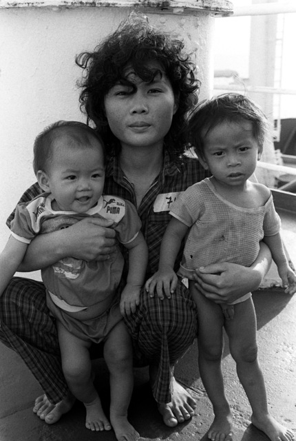 A Vietnamese refugee mother poses for a photograph with her children aboard the petroleum tanker OVERSEAS VIVIAN (T-AOT-2006) as the ship arrives in port at Naval Base, Subic Bay. The commercial tanker, which is operating under a charter with the Navy's Military Sealift Command, is transporting 109 Vietnamese refugees to Naval Base, Subic Bay, following their recovery from a disabled boat in the South China Sea on April 20th. Exact Date Shot Unknown