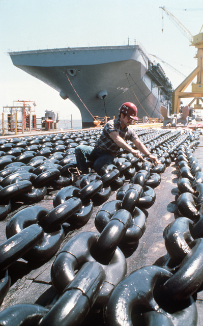 A workman inspects the anchor chain of the Amphibious Assault Ship USS WASP (LHD 1) as the ship sits in dry dock following completion at Ingalls Shipbuilding.  The first ship in its class, WASP combines flight deck and well deck capabilities with a state-of-the-art combat information center and several newly develped systems