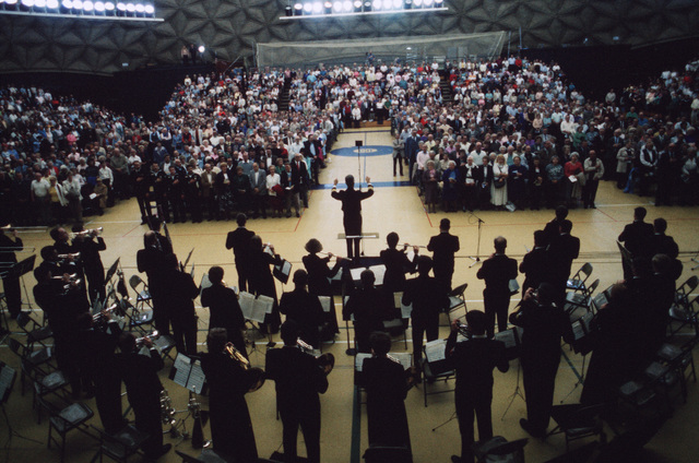At the beginning of a US Navy Band concert, conductor Commander (CDR) Allen Beck leads the audience in a rendition of the national anthem.  The concert is taking place during the band's national tour