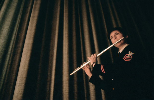 CHIEF Musician (MUC) Peggy Carr warms up on her flute backstage before a concert during the US Navy Band's national tour