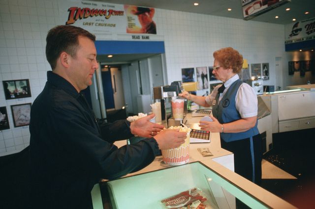 CHIEF Musician (MUC) Robert Snider, a drummer in the US Navy Band, picks up popcorn and a soft drink before seeing a movie during one of the band's rare breaks on its national tour