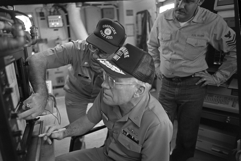 On board the craft-of-opportunity program (COOP) trainer CT-11, Rear Admiral (RADM) Neale Smith, sitting, commander, Naval Reserve Force, looks at a printout as SENIOR CHIEF (SCPO) Mark C. Mager explains the computer-generator picture of the bay floor that it presents. COOP trainers are converted small craft equipped with gear that allows them to survey harbor bottoms and detect mines