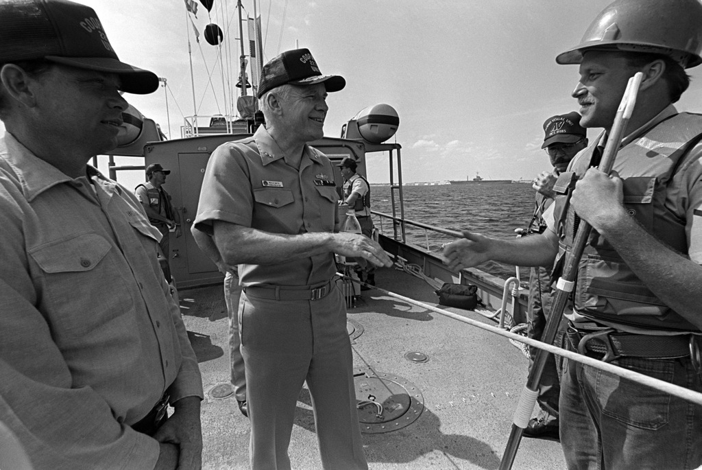 Rear Admiral Neale Smith, center, commander, Naval Reserve Force, congratulates crew members of the craft-of-opportunity program (COOP) trainer CT-11 after a successful search operation. COOP trainers are converted small craft equipped with gear that allows them to survey harbor bottoms and detect mines