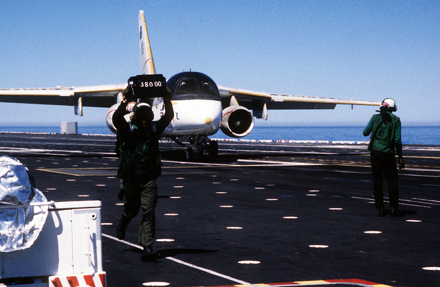 A flight deck crewman flashes a tote board indicating the weight of an S-3A Viking aircraft of Air Anti-submarine Squadron 41 (VS-41), as it moves up to the catapult prior to takeoff during Reserve Carrier Air Wing 30 (CVWR-30) qualifications aboard the Aircraft Carrier USS INDEPENDENCE (CV 62)