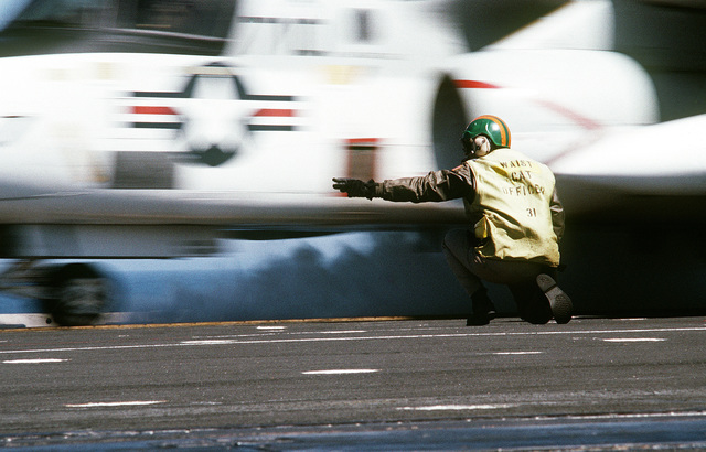 A kneeling catapult officer gives the launch signal to an S-3A Viking aircraft of Air Anti-submarine Squadron 41 (VS-41) during Reserve Carrier Air Wing 30 (CVWR-30) qualifications aboard the Aircraft Carrier USS INDEPENDENCE (CV 62)