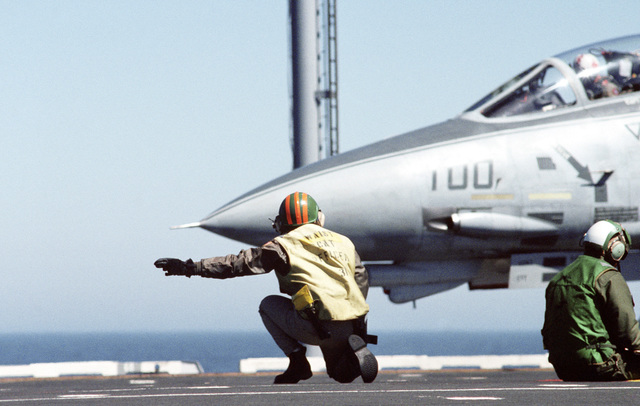 The catapult officer gives the launch signal to the catapult crew and the pilot of an F-14A Tomcat aircraft on the flight deck of the aircraft carrier USS INDEPENDENCE (CV 62).  The aircraft and deck crew are from Reserve Carrier Air Wing 30 (CVWR-30), which is aboard the INDEPENDENCE off the coast of southern California for carrier qualifications