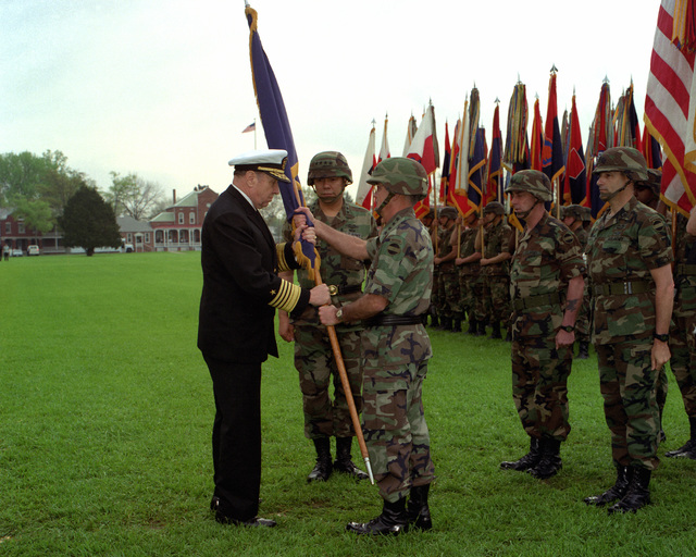 Adm. William Crowe, Jr. passes the ceremonial flag to GEN. Joseph T. Palastra, Jr. as GEN. Colin L. Powell prepares to assume command of Forces Command (FORSCOM). Command SGT. MAJ. Robert F. Beach and Command SGT. MAJ. G.L. Horvath, III participate