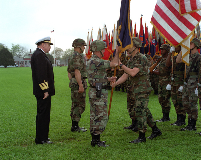 GEN. Joseph T. Palastra, Jr. passes the ceremonial flag to Command SGT. MAJ. Robert F. Beach as GEN. Colin L. Powell prepares to take command of Forces Command. Adm. William J. Crowe looks on