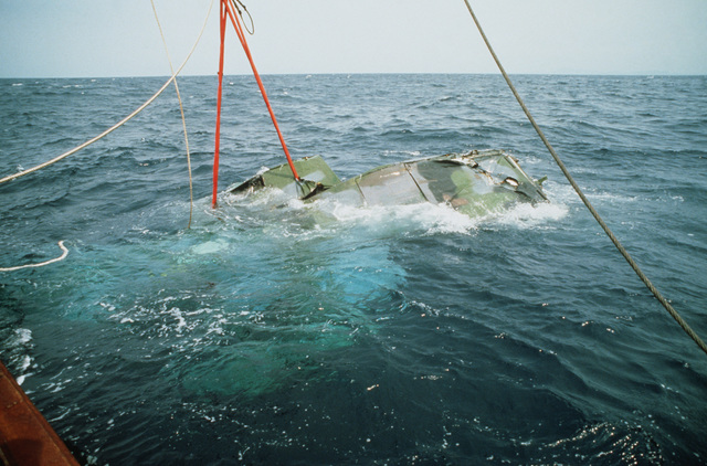 Being lifted from the depths by cranes aboard the Japanese salvage ship SHIN TATSU MARU, an Air Force HH-3E Jolly Green Giant helicopter breaks the surface. The helicopter, which crashed 5.6 miles off the coast of Okinawa, had been resting in 1,800 feet o