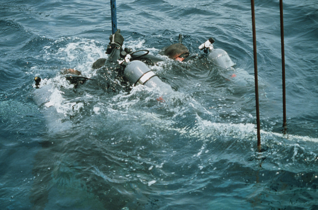 Three Air Force divers keep their eyes on events below the surface as an HH-3E Jolly Green Giant helicopter is hoisted from the depths by a crane aboard the Japanese salvage ship, SHIN TATSU MARU.  The Air Force helicopter, which crashed into the sea 5.6