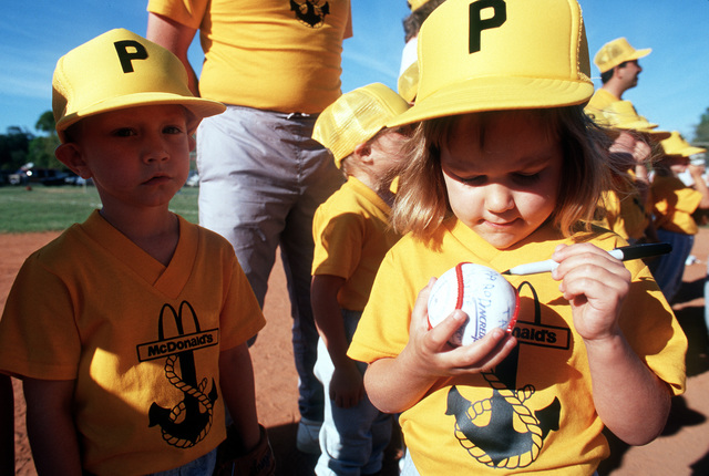 A member of a T-ball team autographs a ball as a teammate stands by following a game at the naval air station. Volunteers from the station host youth activities as part of their community involvement program