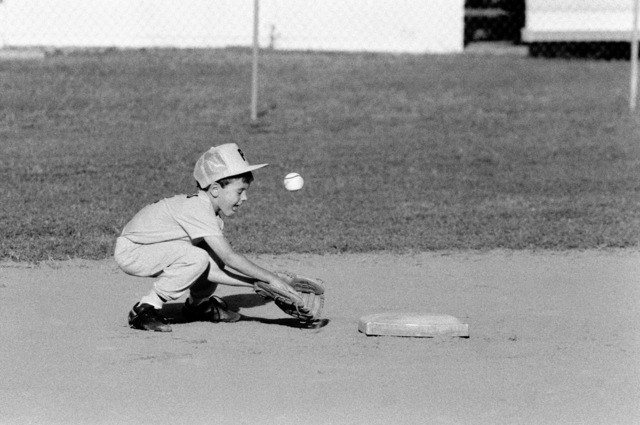 A second baseman fumbles in his attempt to field the ball during a T-ball game at the naval air station.  Volunteers from the station host youth activities as part of their community involvement program