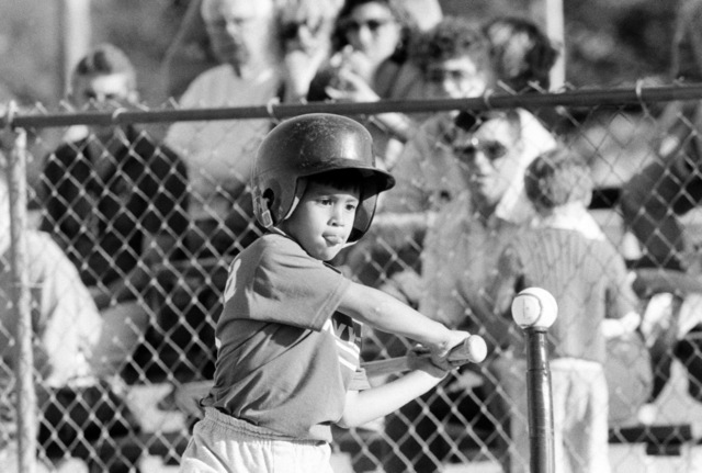 A T-ball player concentrates as he takes a swing during a game at the naval air station recreational facility.  Volunteers from the station host youth activities as part of their community involvement program