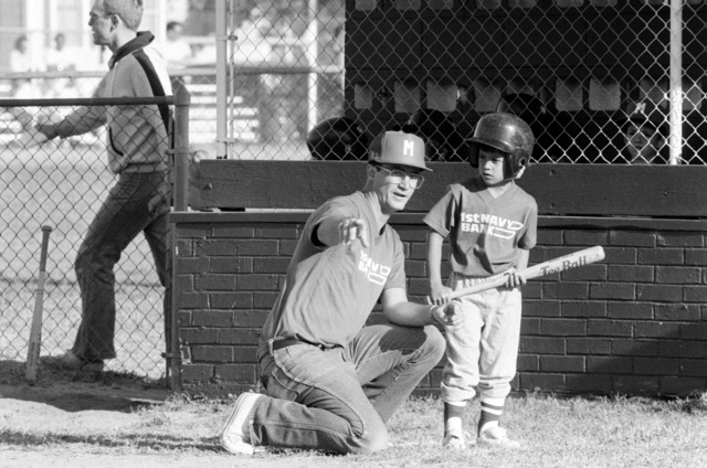 A volunteer from the naval air station coaches a T-ball player as part of the station's community involvement program