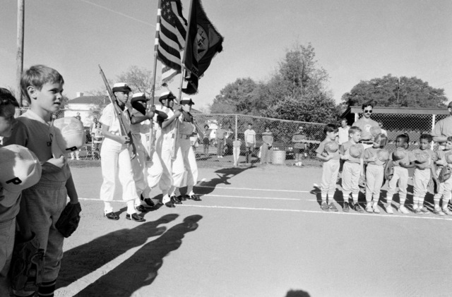Members of a T-ball team stand with caps removed as the colors are presented prior to a game at the naval air station.  Volunteers from the station host youth activities as part of their community involvement program