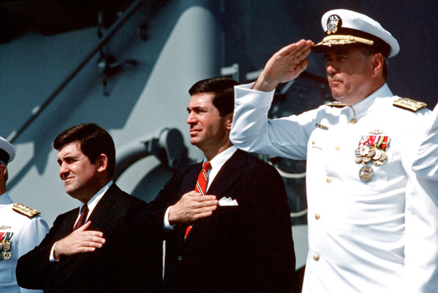 Rendering salutes during the commissioning ceremony for the dock landing ship USS GUNSTON HALL (LSD 44) are, from left to right, Secretary of the Navy William L. Ball III; Senator Charles S. Robb of Virginia; and Vice Admiral (VADM) Joseph S. Donnell III, commander, Naval Surface Force, US Atlantic Fleet