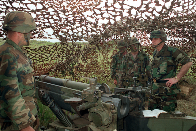 Army CHIEF of STAFF General (GEN) Carl E. Vuono, right, stands near an M102 105 mm howitzer as he listens to a captain with the 25th Infantry Division. (Light) explaining an upcoming direct-fire exercise