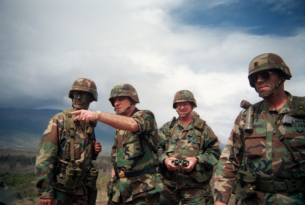 Army CHIEF of STAFF General (GEN) Carl E. Vuono, second from left, makes a point while speaking with a lieutenant from the 25th Infantry Division (Light), during a visit to the training area. Accompanying the general is Major General (MGEN) Charles P. Ots