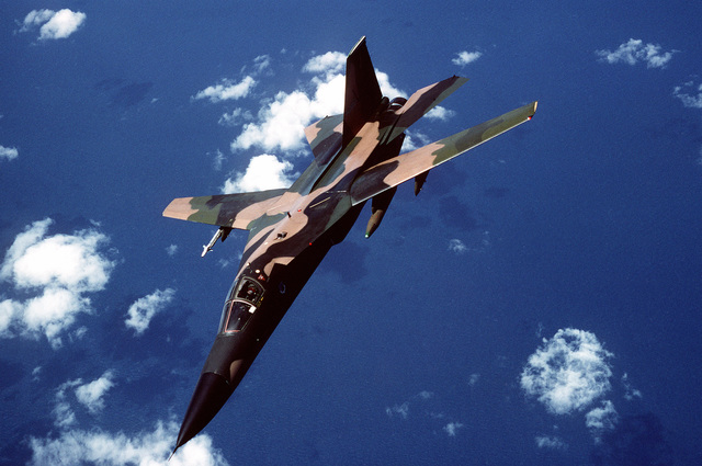 An air-to-air left front view of a 495th Tactical Fighter Squadron F-111F aircraft flying a mission out of Moron Air Base, Spain, during Open Gate '89. Open Gate is a Joint Chiefs of STAFF/NATO Exercise designed to simulate air and sea power tactics required to keep the Straits of Gibraltar open during a crisis