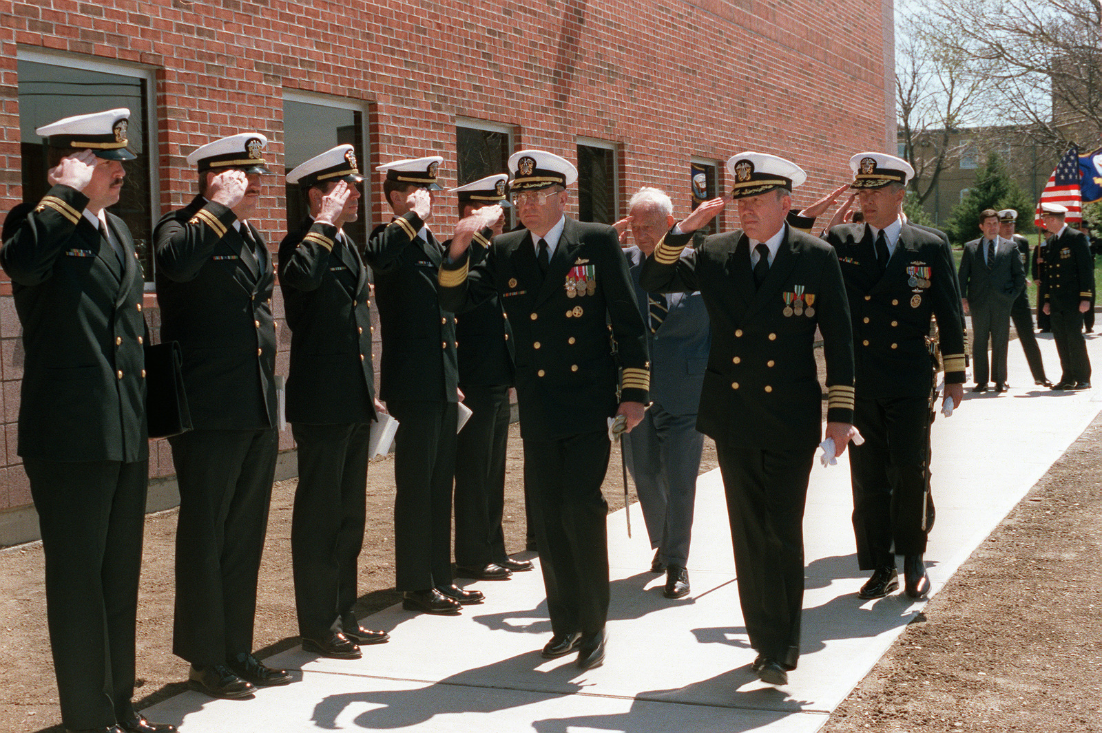 A line of lieutenants salutes a passing group of senior officers attending the dedication ceremony for Arleigh Burke Hall at the Naval War College. The hall's namesake, retired Admiral (ADM) Arleigh A. Burke, a former chief of naval operations, can be seen in the second rank of passing officers, between the two admirals