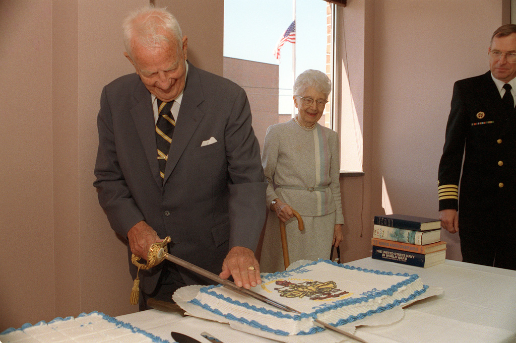 Retired Admiral (ADM) Arleigh A. Burke, a former chief of naval operations, uses a ceremonial sword to cut a cake commemorating the dedication of a hall named in his honor at the Naval War College as his wife and a captain look on