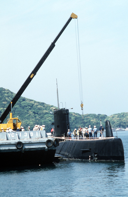 The attack submarine USS DARTER (SS 576) is docked at the pier in preparation for an ammunition loading at the Maebata Ordnance Facility
