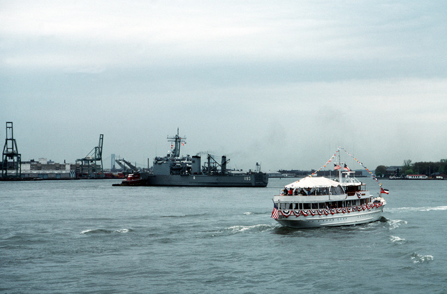 A civilian vessel approaches the tank landing ship USS FAIRFAX COUNTY (LST 1193), which is being maneuvered into a berth at the start of Fleet Week