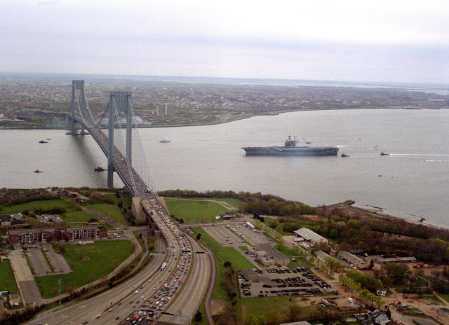 The aircraft carrier USS FORRESTAL (CV-59) approaches the Verrazano Narrows Bridge as it makes its way into New York City. The FORRESTAL and its battle group are visiting the city to participate in Fleet Week '89