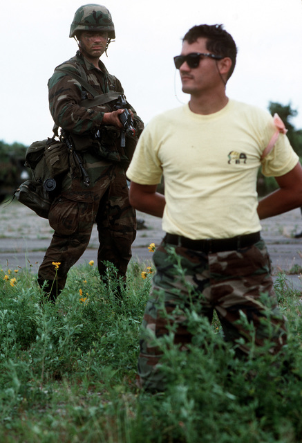 "A 1ST Bn., 504th Parachute Infantry Regt., 82nd Airborne Div. ""Blue Forces"" soldier takes a prisoner as the ""Red Forces"" Marine defenders of Atlantic airfield are overcome during exercise Solid Shield '89. The exercise is being conducted on the East Coast of the United States by approximately 30,000 military personnel from all services"