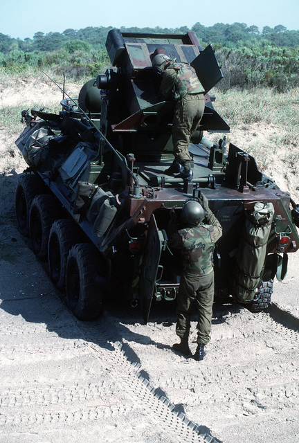 A crewman services the tube-launched, optically tracked, wire-guided (TOW) anti-tank missile launcher mounted atop an LAV-25 light armored vehicle (LAV) during the joint services Exercise Solid Shield '89