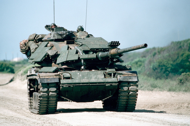 A Marine Corps M60 main battle tank with reactive armor bolted to its hull and turret moves inland after coming ashore on D-Day of the joint services exercise SOLID SHIELD '89