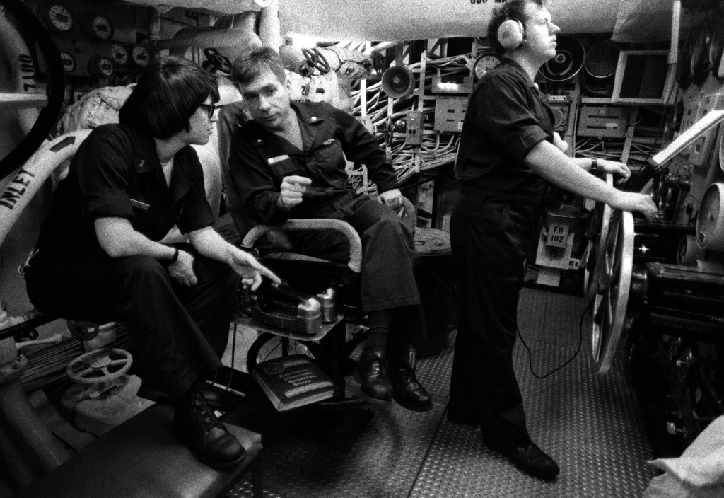 Machinist's Mate 3rd Class Tom Long, throttleman, operates controls while CMDR. Harry Elam, chief engineering officer, speaks with LT. j.g. Gail Zeisser, engineering officer of the watch, aboard the training aircraft carrier USS LEXINGTON (AVT-16). The LEXINGTON is the Navy's oldest commissioned carrier