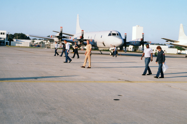 Members of Naval Air Reserve Patrol Squadron 68 (VP-68) scan the airfield for debris that could cause foreign object damage to their P-3B Orion aircraft, one of which sits parked behind them.  VP-68 is in Rota for active duty training