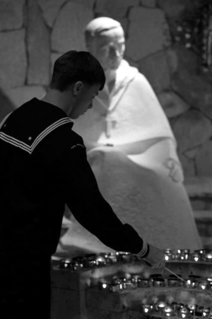 Photographer's Mate AIRMAN Apprentice Glen Albarado lights a votive candle inside Saint Patrick's Cathedral while on liberty during Fleet Week
