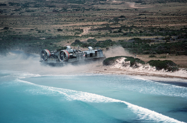 The Landing Craft Air Cushion LCAC-10 kicks up a cloud of sand and dust as it comes ashore with a load of Marine Corps equipment and trucks.  The landing craft is operating with 6th Fleet amphibious forces in the Mediterranean Sea area