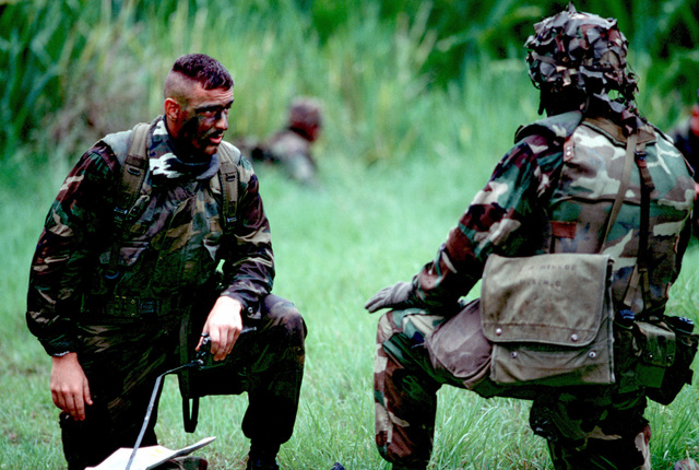 Two servicemen pause over a map during jungle training
